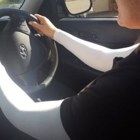 A woman driving a car and wearing IceRays Sun Sleeves for sun protection from harmful UV rays while driving. Driving