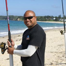 A man standing on the beach beside fishing poles wearing IceRays Sun Sleeves for Maximum sun protection while fishing. Fishing