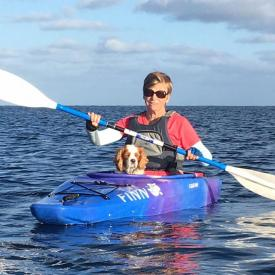 A woman kayaking with her dog and wearing IceRays Sun Sleeves for Maximum UV sun protection while paddling on the water. Kayaking