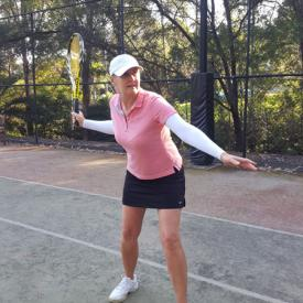 A woman about to hit a forehand tennis stroke wearing IceRays Sun Sleeves to protect her arms from the sun while playing tennis. Sun Protection! Tennis